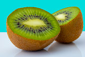 A delicious kiwi cut in half on a table with reflection and a cheerful background