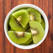 Top view of white bowl full of sliced kiwi