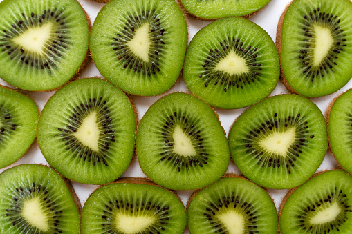 a box of fresh kiwis for sale on a market stall