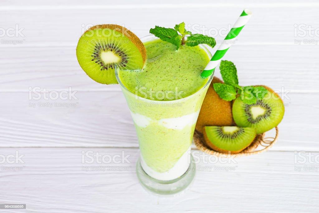 Sucos de smoothies Kiwi iogurte e verde kiwi fruta, bebida saudável o gosto gostoso em vidro para milk-shake em fundo branco de madeira. - Foto de stock de Alimentação Saudável royalty-free