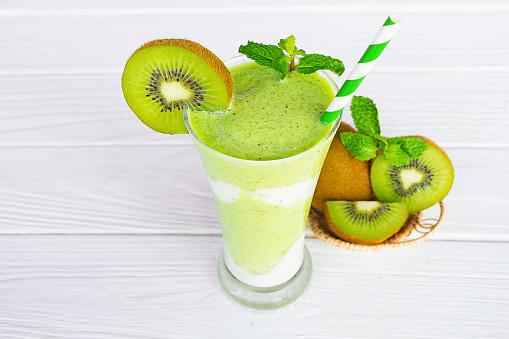 Foto de Sucos De Smoothies Kiwi Iogurte E Verde Kiwi Fruta Bebida Saudável O Gosto Gostoso Em Vidro Para Milkshake Em Fundo Branco De Madeira e mais fotos de stock de Alimentação Saudável