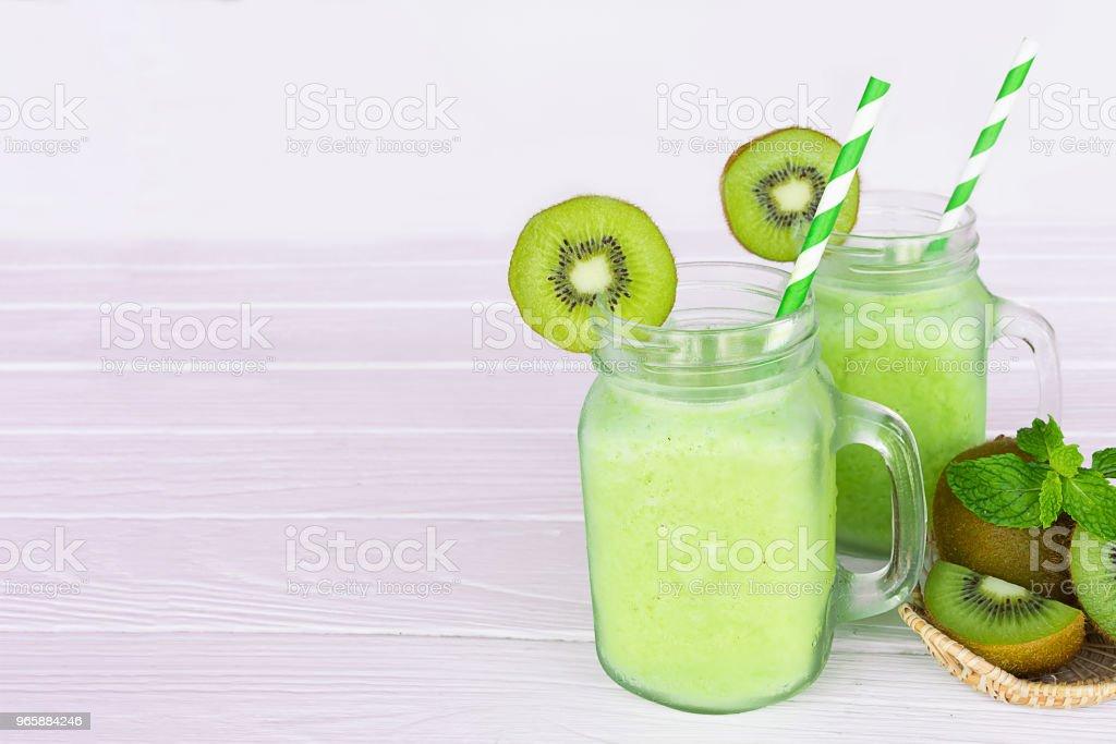 Kiwi yoghurt smoothies sappen en kiwi groen fruit gezond drankje de smaak lekker in glas voor voor milkshake op houten witte achtergrond. - Royalty-free Bes Stockfoto