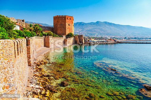 istock Kizil Kule tower in Alanya peninsula, Antalya district, Turkey, Asia. Famous tourist destination with high mountains. Part of ancient old Castle. Summer bright day 821804760