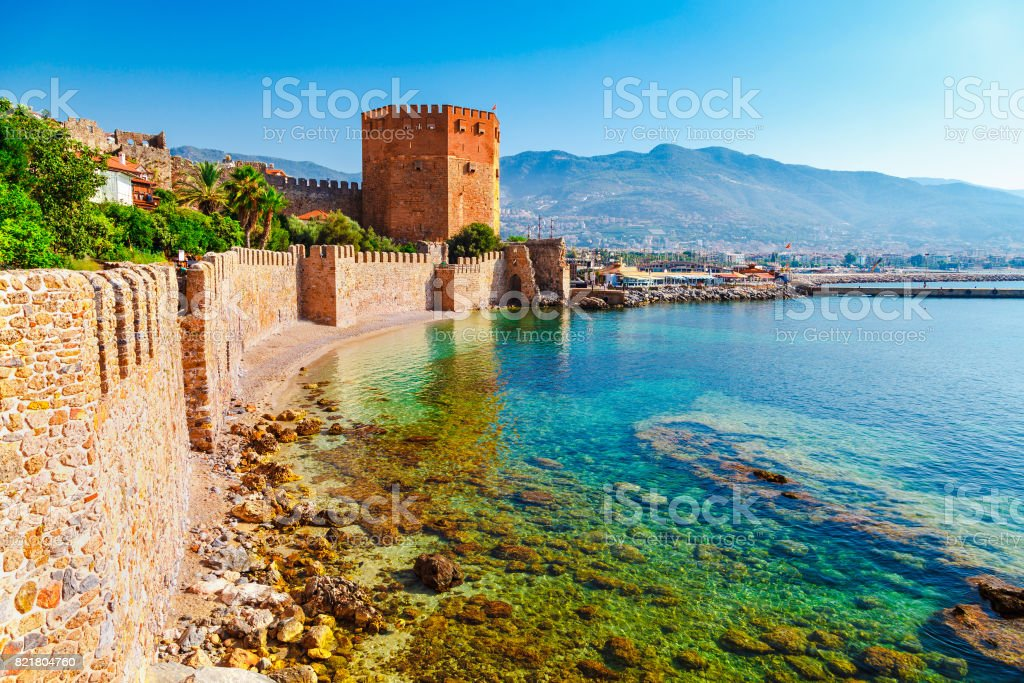 Kizil Kule tower in Alanya peninsula, Antalya district, Turkey, Asia. Famous tourist destination with high mountains. Part of ancient old Castle. Summer bright day stock photo