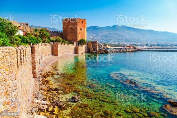 Kizil Kule tower in Alanya peninsula, Antalya district, Turkey, Asia. Famous tourist destination with high mountains. Part of ancient old Castle. Summer bright day