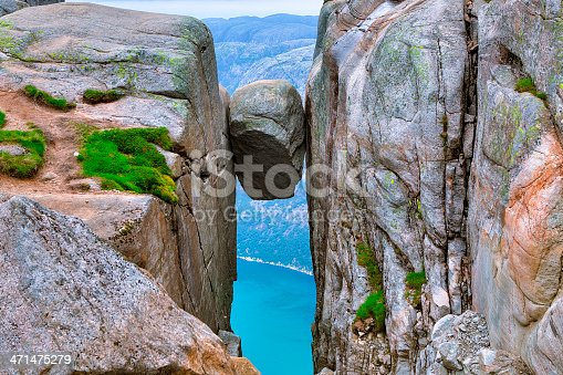 A massive bounder that's wedged and completely stuck between the walls of two steep cliffs in Kjerag Mountains, Norway