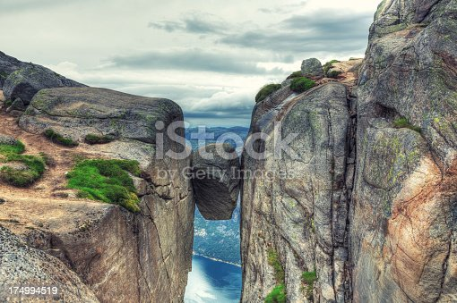 Famous rock wedged and completely stuck between the walls of two steep cliffs in Kjerag Mountains, Norway