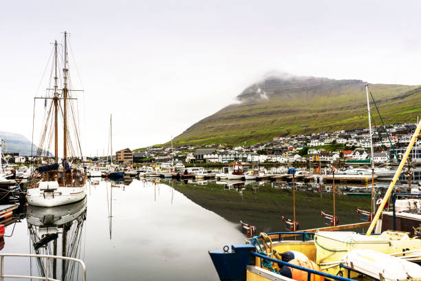 Klaksvik port full of fishing boats and green mountains on the other side of fjord. Faroe Islands. stock photo