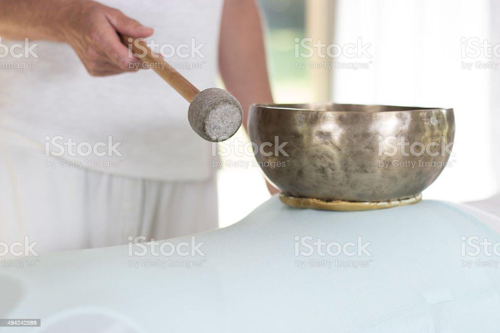 Klangschalenbehandlung am Rücken einer Frau stock photo