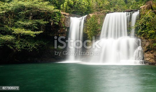 Klong Chao waterfall serenely cascades into the tranquil green pool below. It is located in the interior of the island of Koh Kood, Thailand.