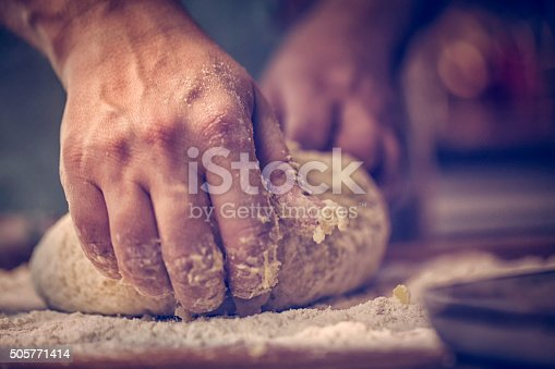 Kneading dough with hands on the table to prepare delicious bakery goods.