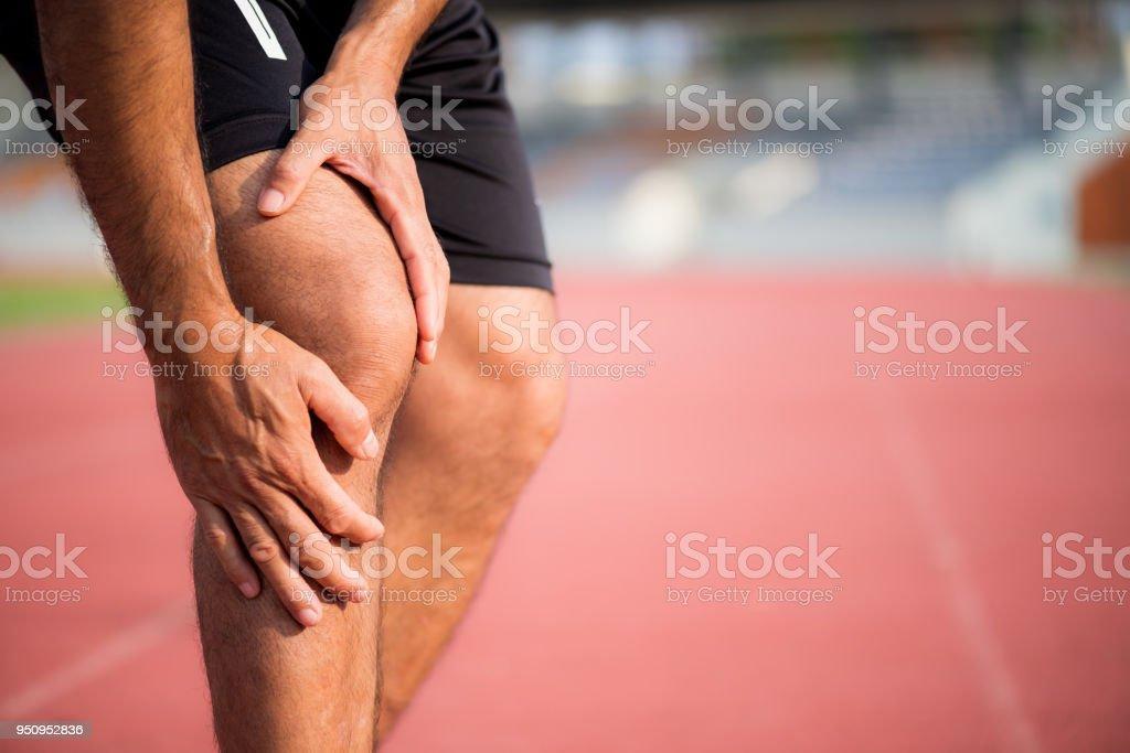 Knie-Verletzungen. junge Sportler mit starken sportlichen Beinen, die Knie mit den Händen nach Leiden Muskelverletzung während einer Training Lauftraining auf Laufstrecke in Schmerz zu halten. – Foto