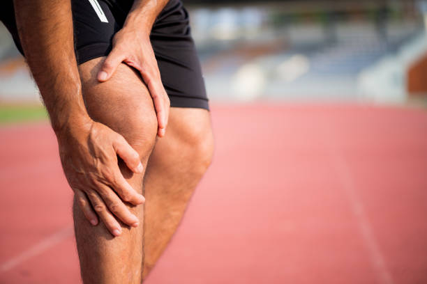 knee injuries. young sport man with strong athletic legs holding knee with his hands in pain after suffering muscle injury during a running workout training on running track. - sports medicine stock photos and pictures
