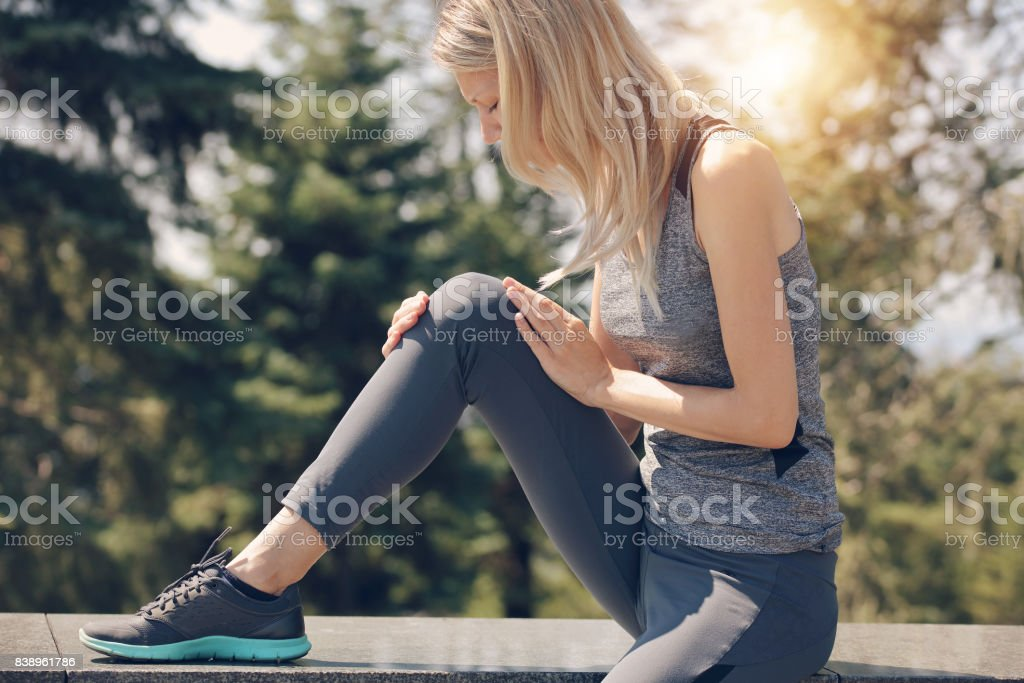 Knee injury, Woman runner with knee pain outdoor stock photo