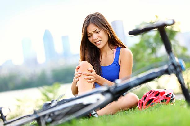 Knee pain bike injury woman stock photo