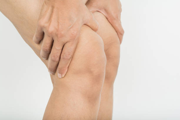knee pain in woman stock photo