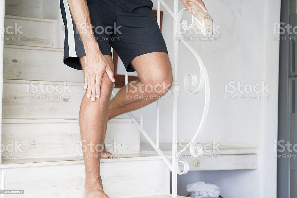 Knee pain on stairs stock photo