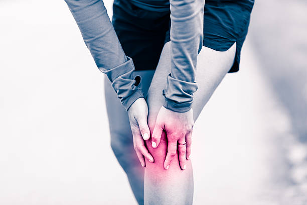 Knee pain, woman holding sore and painful leg stock photo