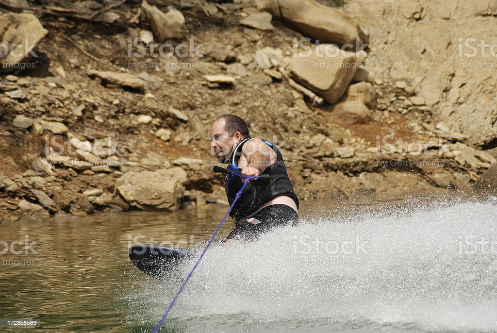 Kneeboarding One Handed By Rocks royalty-free stock photo