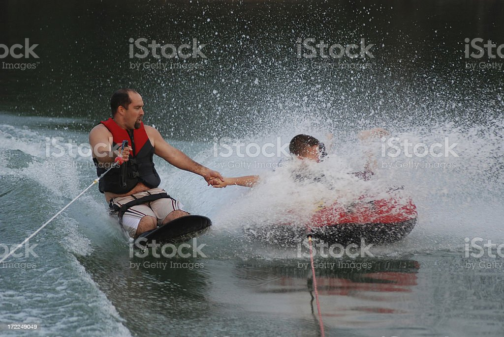 Kneeboarding with Dad While Tubing royalty-free stock photo