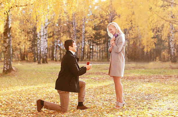 Kneeled man proposing ring to a woman in autumn park stock photo