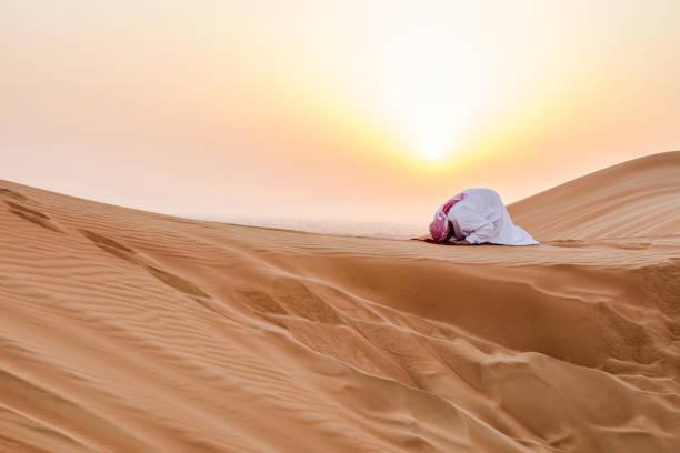 무릎을 꿇 고 하나님 앞에 기도 일출 동안. - saudi national day 뉴스 사진 이미지