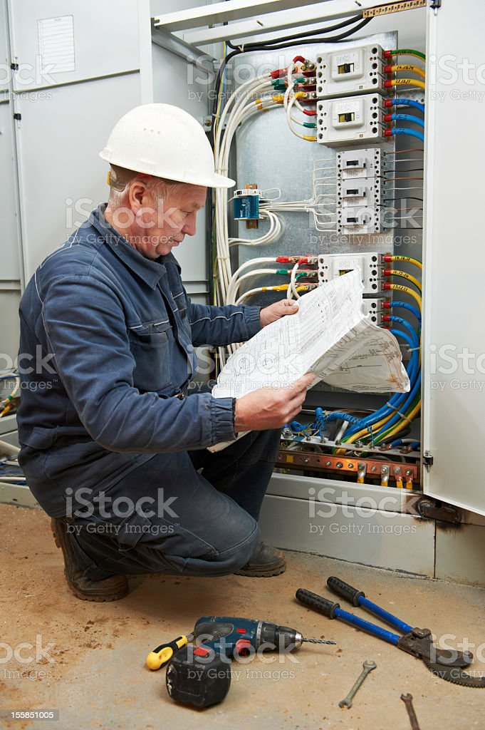 kneeling electrician looking at drawings and wiring at work stock rh istockphoto com wiring technician avg pay mississippi AT&T Van