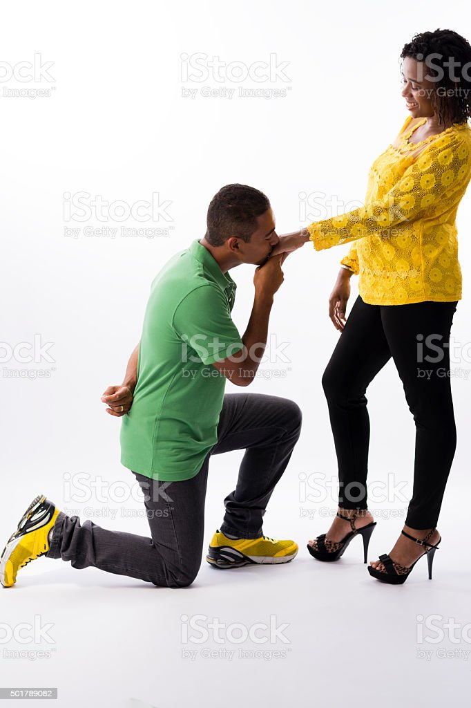 Kneeling man kissing his wife's hand stock photo