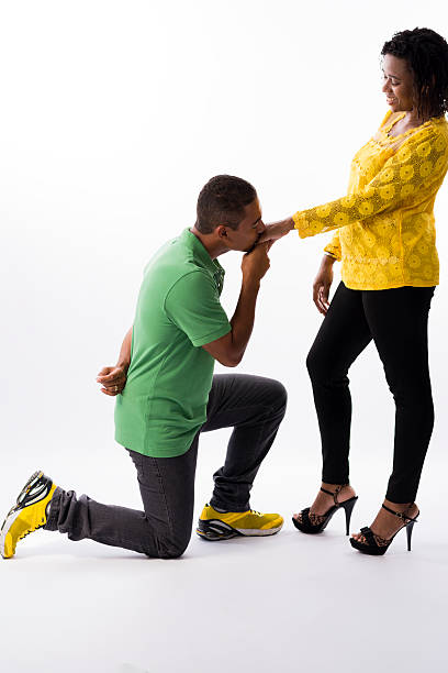 Kneeling man kissing his wife's hand Brazilian couple. Kneeling man, like a gentlelman, kissing his wife's hand. The woman is wearing heels, standing, and looking for the man. kissinghand stock pictures, royalty-free photos & images