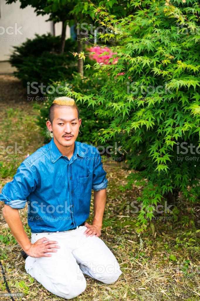 Kniender Mann Mit Irokesen Frisur Im Park Japan Stockfoto Und Mehr