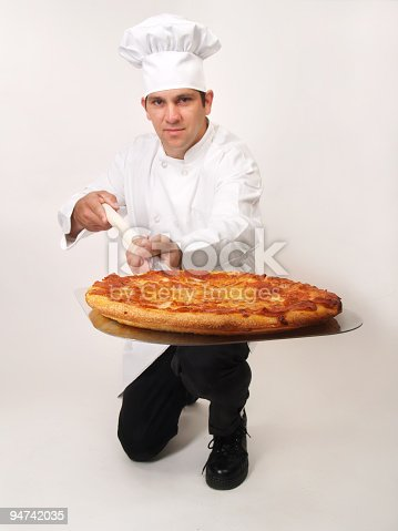 Full view of pizza chef kneeling and serving a pepperoni pizza on his huge spatula; focus on pizza and man is slightly out of focus; copy space