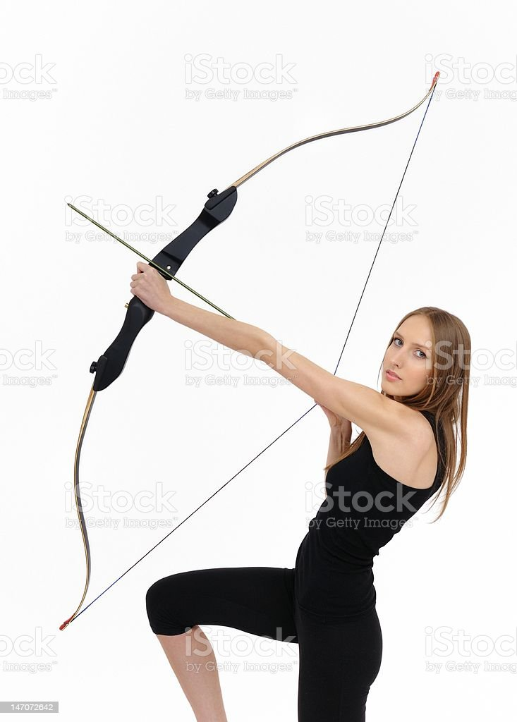 Kneeling woman shooting with bow stock photo