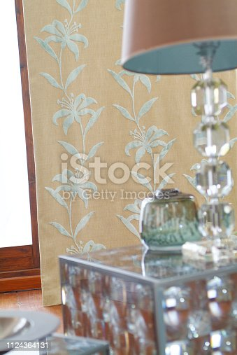 Side table cabinet with electric lamp by floral patterned wall