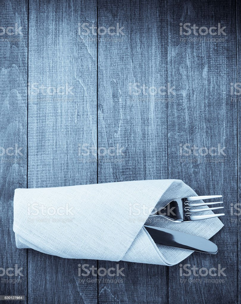 knife and fork at napkin on wood stock photo