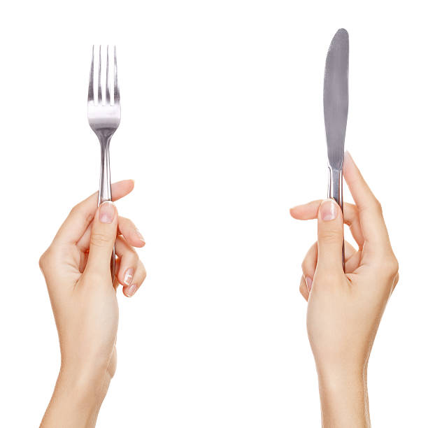 knife and fork being held by womans hands. Isolated stock photo