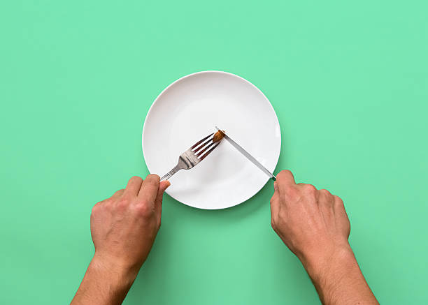 knife and fork cutting into small diet meal on white plate - 食用份量 個照片及圖片檔