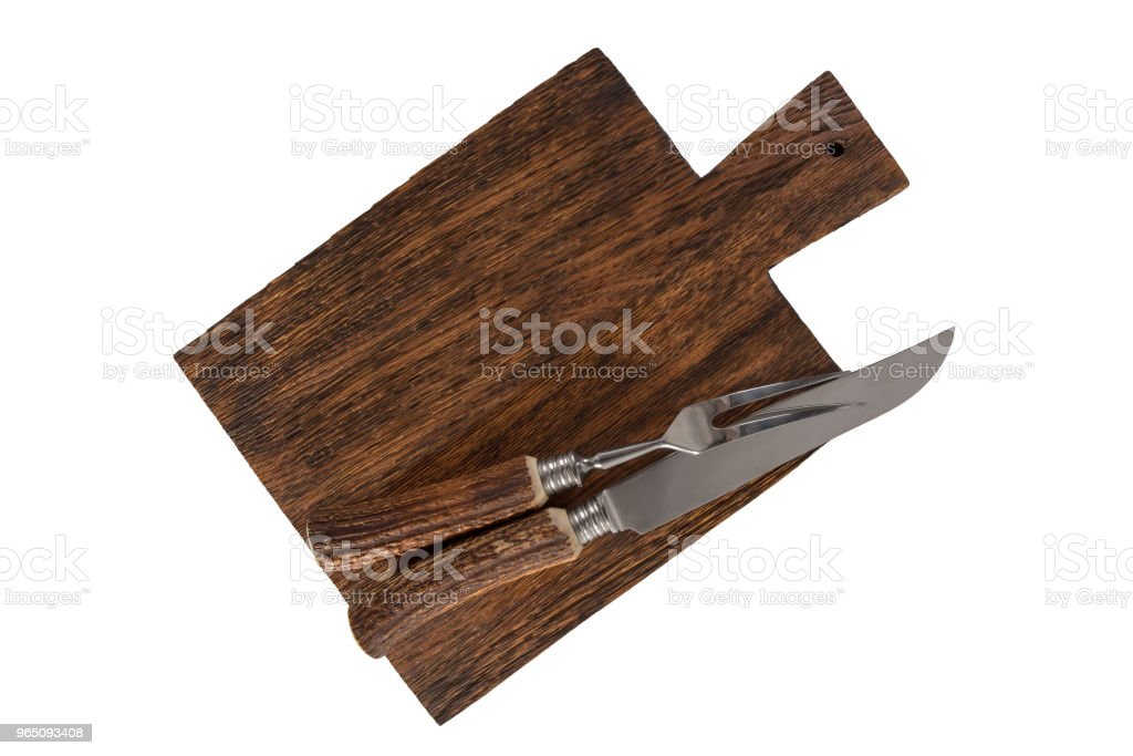 Knife and fork for cutting meat on a board isolated on white background. zbiór zdjęć royalty-free