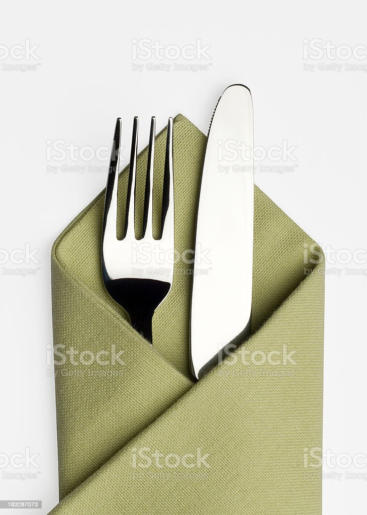 Knife and fork in a green napkin stock photo