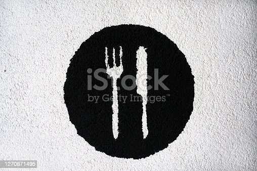 Knife and fork on a black plate are depicted on the plastered wall.
