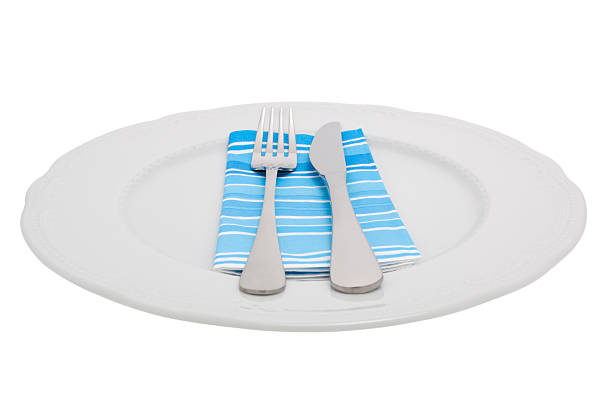 knife and fork on a plate - blue table setting stock photos and pictures