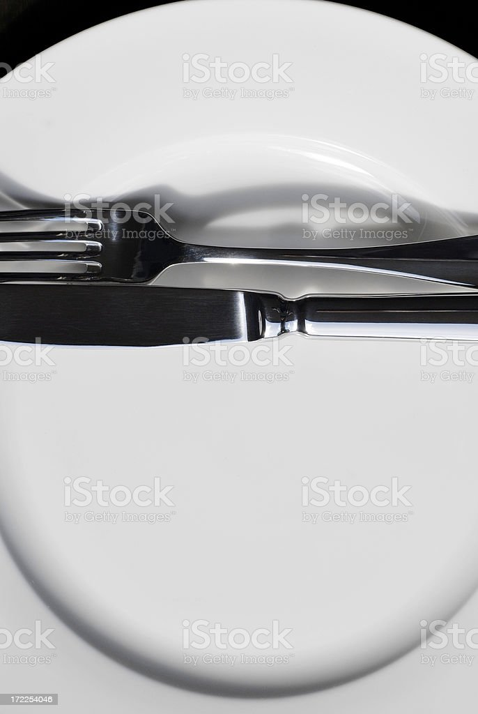 Knife and fork on an empty white plate royalty-free stock photo