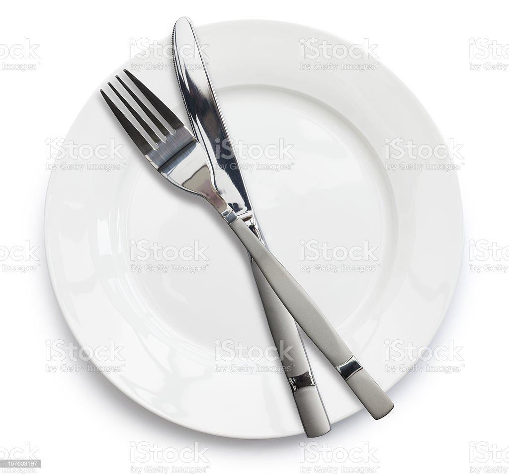 Knife and fork on empty white plate stock photo