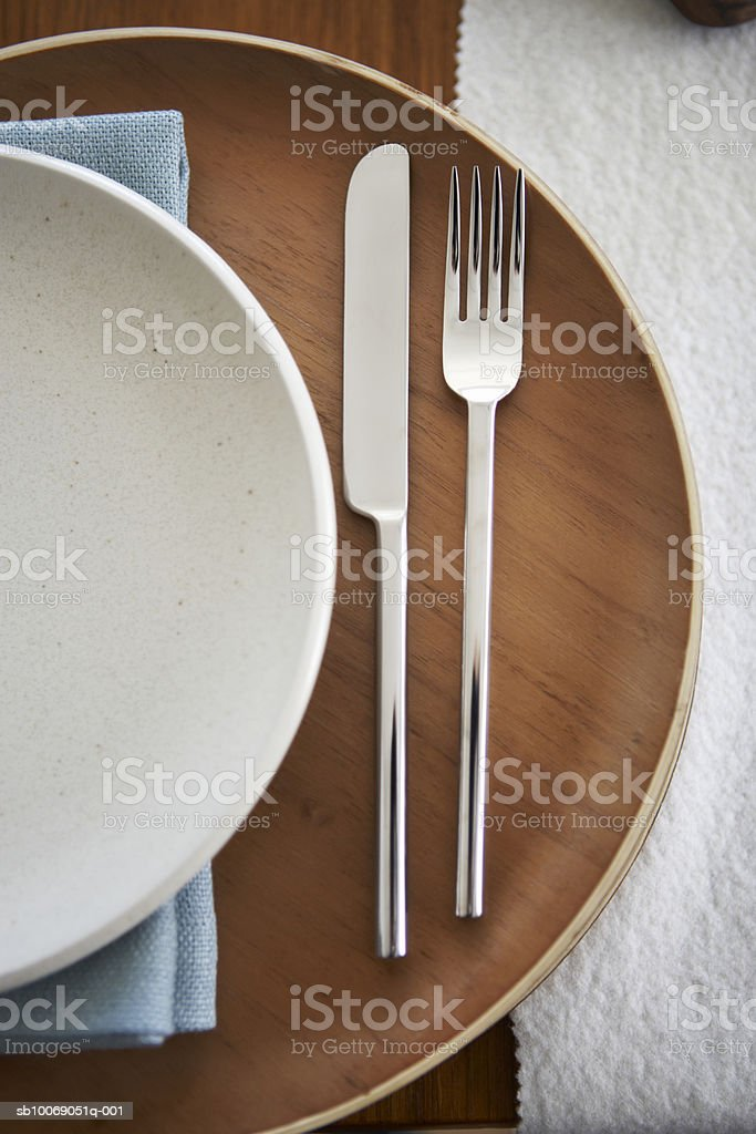 Knife and fork on wooden plate, view from above, close-up Lizenzfreies stock-foto