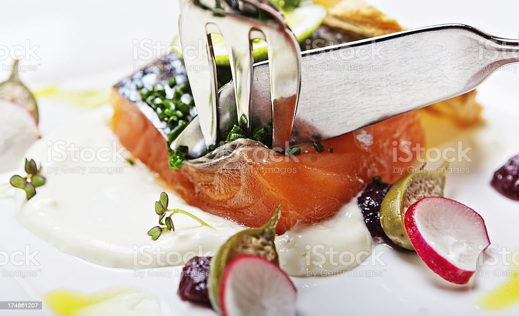 Knife and fork pierce salmon dish in restaurant royalty-free stock photo