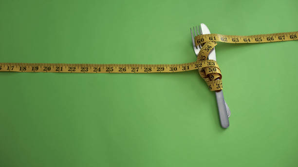 Knife and fork tied with measuring tape, concept of strict food restrictions Knife and fork tied with measuring tape, concept of strict food restrictions anorexia nervosa stock pictures, royalty-free photos & images