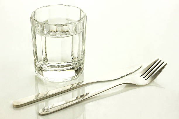 Knife and fork with a glass of water stock photo
