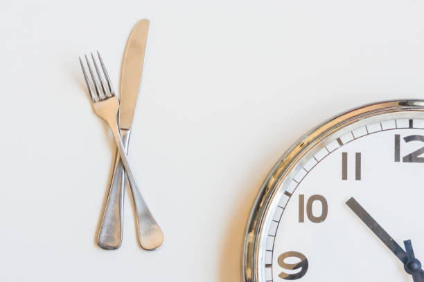 Knife and fork with clock on white background stock photo