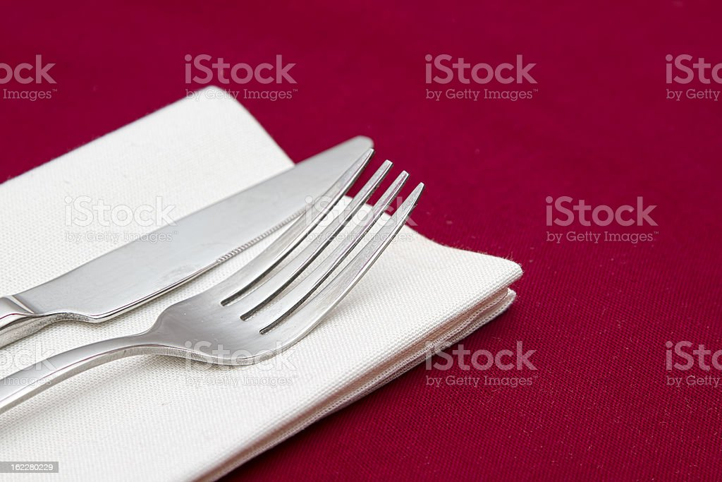 Knife and fork with white napkin on red tablecloth royalty-free stock photo