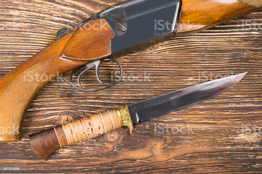 Knife and gun for the hunter lie on a beautiful table stock photo