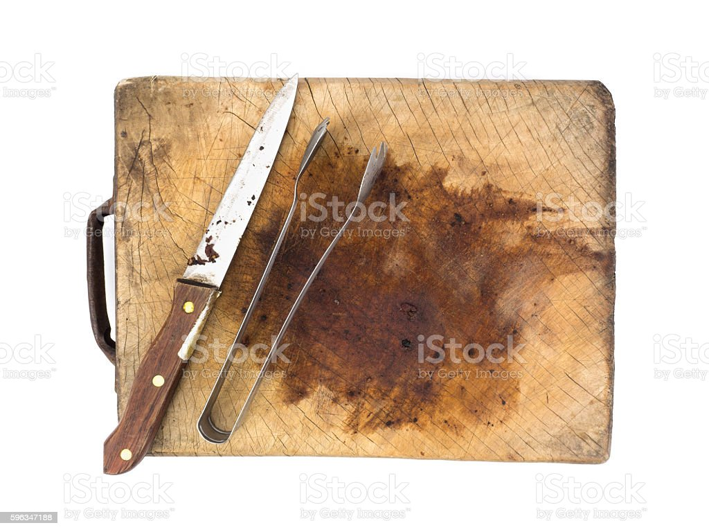 Knife and tongs on a wooden chopping board royalty-free stock photo